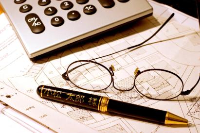 図面と電卓、眼鏡とあなたのお名前入り高級ボールペン。